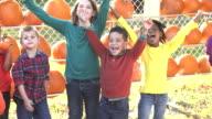 Multi-ethnic children playing, pumpkins behind them