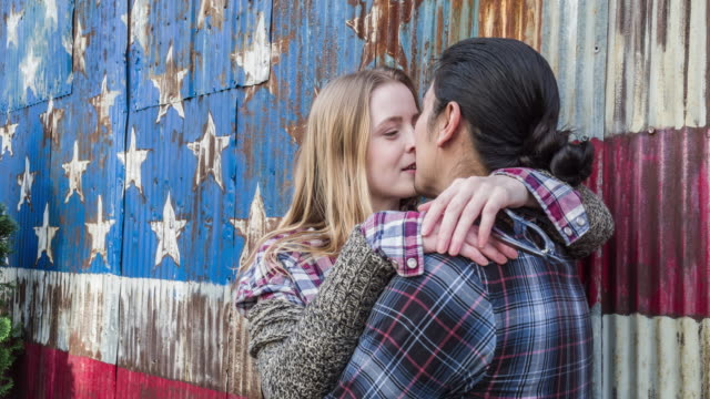 Multi-ethnic couple kissing in the street