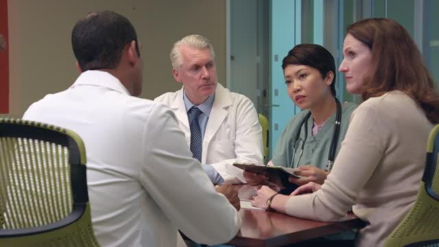 Multi-Ethnic Doctors Meet in Modern Office - MS