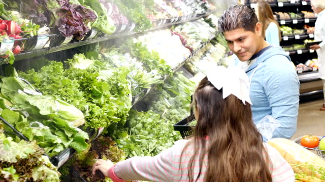 Multi-ethnic family shopping for produce in local supermarket