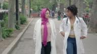 Multi-etnische vrouwelijke medische Professionals lopen samen