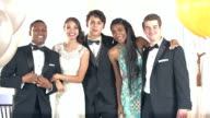 Multi-ethnic friends dressed for prom posing for photos