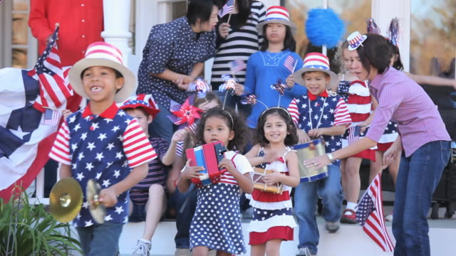 MS Multi-ethnic group celebrating Independence Day, children walking in parade in back yard / Richmond, Virginia, USA