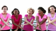 Multi-ethnic group of happy women wearing pink, in a row