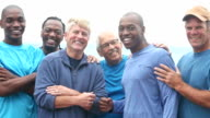 Multi-ethnic group of men in blue smiling at camera
