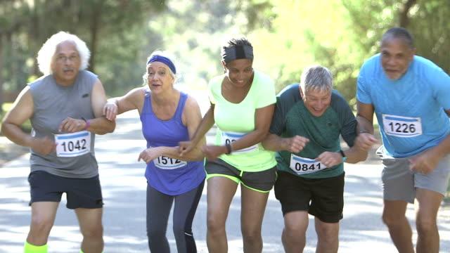 Multi-ethnic group of seniors running in race