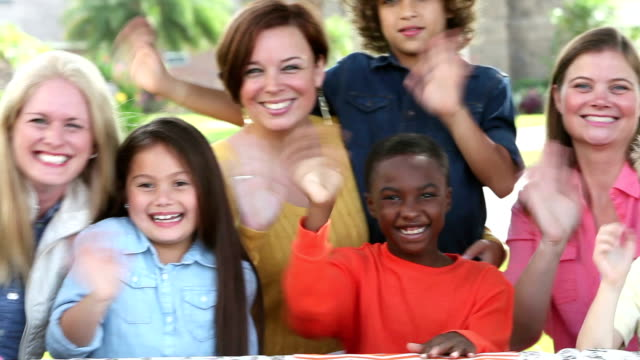 Multi-ethnic group of women, children waving at camera