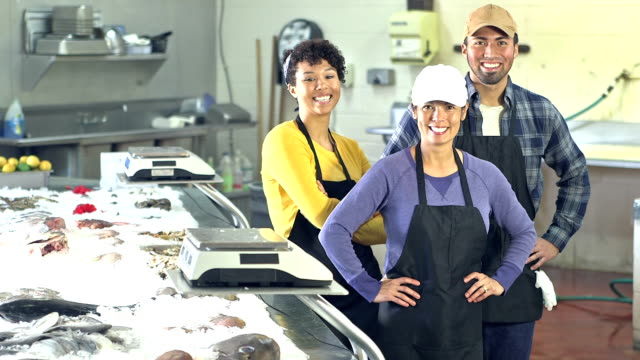 Multi-ethnic group of workers in fish market