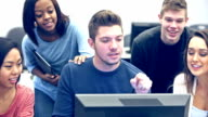 Multi-ethnic high school students in computer class around one monitor