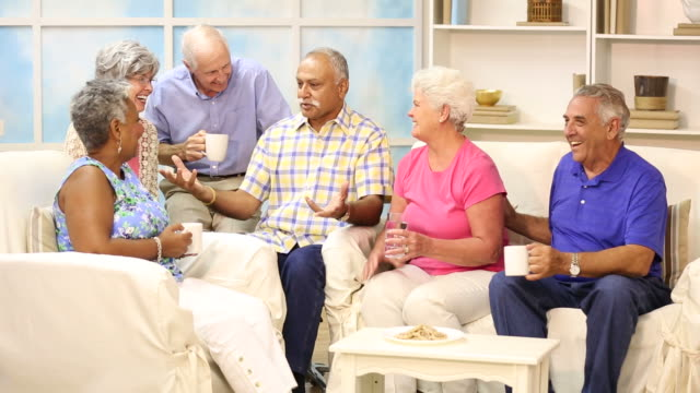 Multi-ethnic senior friends talk, share news at neighbor's home.