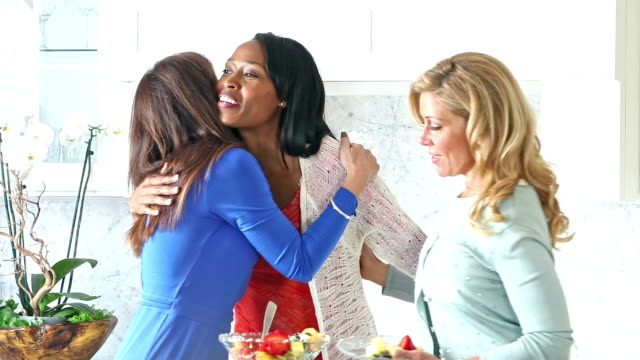 Multi-ethnic women in kitchen greeting, hugging