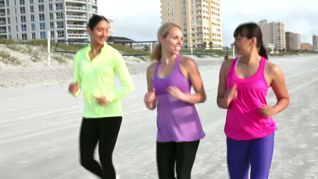 Multi-ethnischen junge Frauen Powerwalking am Strand