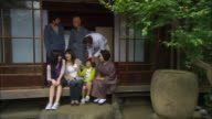 WS PORTRAIT Multigenerational family posing at entrance to house/ Tokyo, Japan