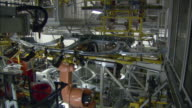 MS Multiple car assembly robots rotate and maneuver car parts into place while constructing single BMW vehicle in car plant / Munich, Bavaria, Germany