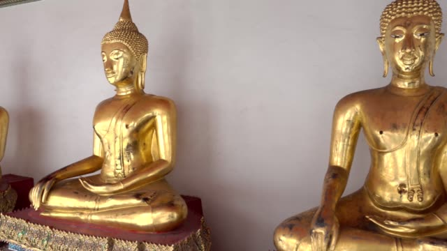 Multiple golden Buddha statues in Wat Pho temple or Temple of the Reclining Buddha, Bangkok Thailand
