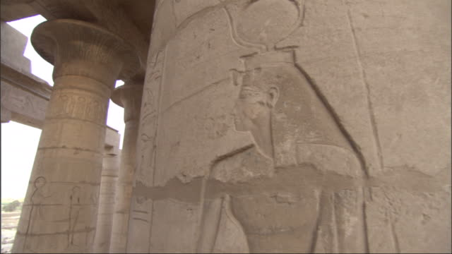 Multiple, pan-left pan-right push-in - Hieroglyphics cover columns and ceiling supports at the ruins of an ancient Egyptian building