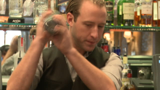 multiple shots CU bartender adding tobasco to drink mixing pouring drink
