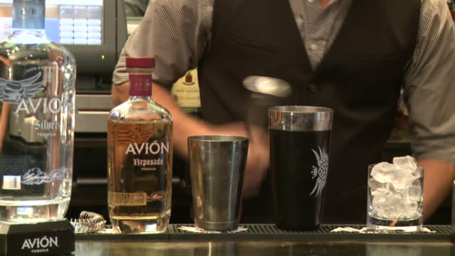 multiple shots CU bartender mixing Avion tequila drink