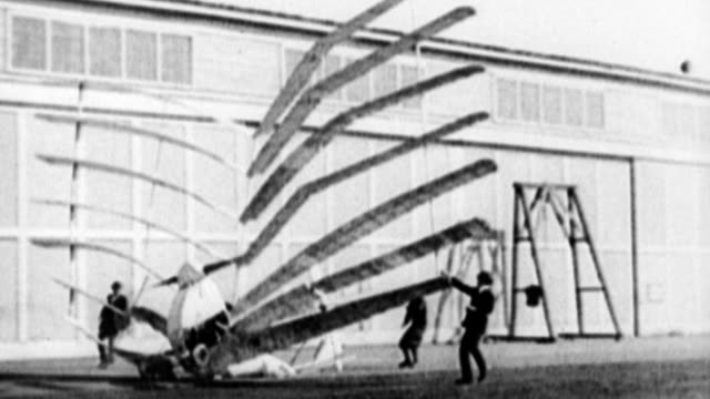 Multiwing airplane with a dozen wings being pushed along until it crumbles and collapses Early failed flight invention on January 01 1915 in...