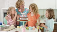 mum and 3 young girls celebrating child's birthday in the kitchen
