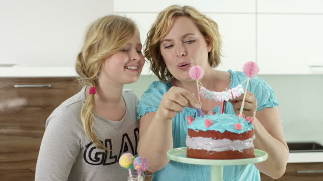 mum and daughter preparing birthday cake with candles