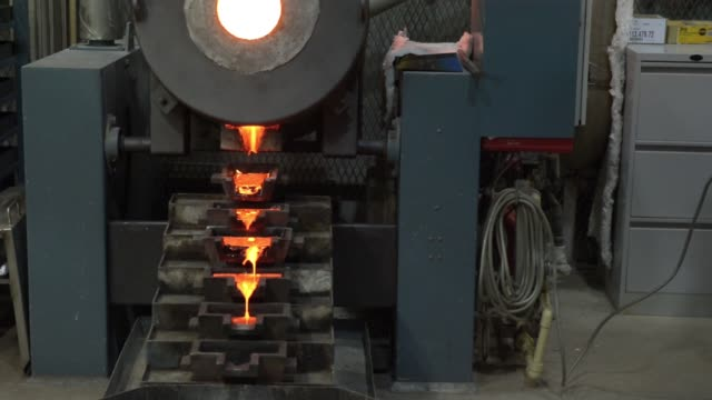 Mungari Australia Wednesday Aug 5 2015 Shots Wide shot Molten gold pours from a crucible into molds at Evolution Mining Ltd's gold operations in...
