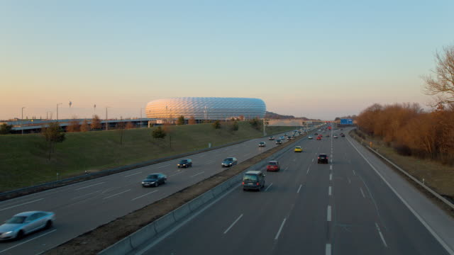 MS T/L Munich football stadium 'Allianz Arena' changing colours and traffic on freeway 'Autobahn' at dusk / Munich, Bavaria, Germany
