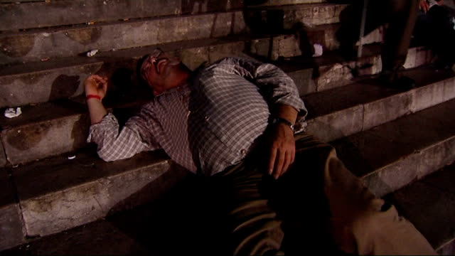 GVs of Oktoberfest beer festival NIGHT Various shots of drunken man lying asleep on steps with empty bottles beside