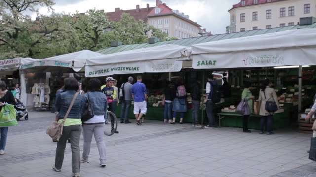 Munich Market, still shot, food stand with shoppers browsing.
