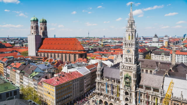 T/L of Munich's townhall at Marienplatz with the famous Frauenkirche next to it, beautiful blue sky with puffy clouds