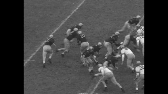WS Municipal Stadium crowd watching 54th annual Army Navy game in Philadelphia / football players on the field / Army cadets on their feet cheering /...