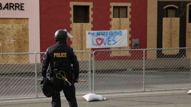 A police officer stands in front of boarded up businesses after White Lives Matter rally participants and others left downtown Murfreesboro Tennessee...