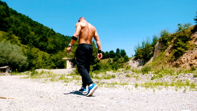 Muscular man walking in the nature