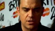 2010 Brit Awards red carpet arrivals Robbie Williams speaking to press / Kylie Minogue speaking to press / Robbie Williams pinching Kylie Minogue's...