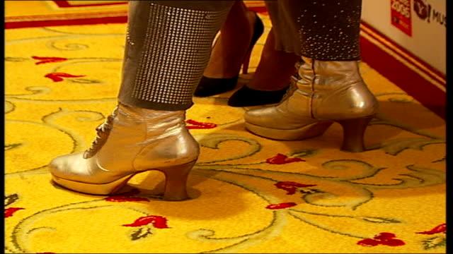 Red carpet arrivals Side view of Boy George posing next Jamelia TILT DOWN Boy George's gold lace up platform shoes TILT UP Boy George posing holding...