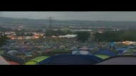 Glastonbury Festival Campers overnight ENGLAND Somerset Glastonbury LAPSE footage of tents as night falls / people milling about next to tents /...