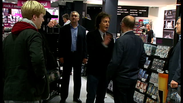 Paul McCartney interview and popup performance Sir Paul McCartney arriving on escalators / McCartney chatting to people in middle of HMV store /...