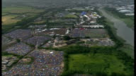 Rain disrupts Isle of Wight Festival ENGLAND Isle of Wight VIEWS / AERIALS traffic jam along road / cars parked in muddy fields / tents and campsite...