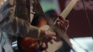 Musician plays electric guitar on stage with band in Austin bar
