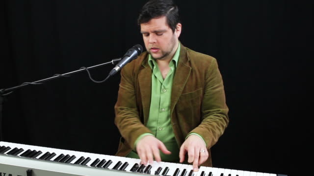 Musician sings into microphone