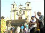 Musicians in blue berets lead procession past foot of church steps Ouro Preto Brazil