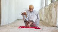 HD DOLLY: Muslim Man Reading Koran On Prayer Mat