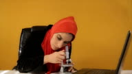 Muslim woman watching through microscope,biologist -professional occupation