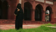 A Muslim woman wears a hijab as she stands near the Jama Masjid mosque. Available in HD.