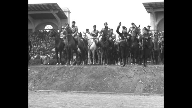 Mussolini rides horse into stadium accompanied by Fascist officers riding horses / crowd of Junior Blackshirts giving Fascist salute / Mussolini and...
