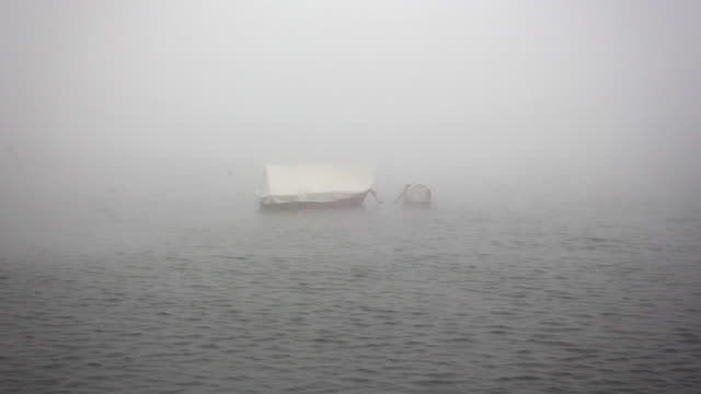 Mysterious boat floating on foggy lake