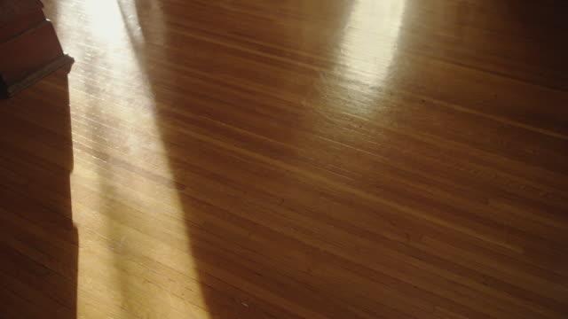 A mysterious human shadow crosses a vintage oak wooden floor.