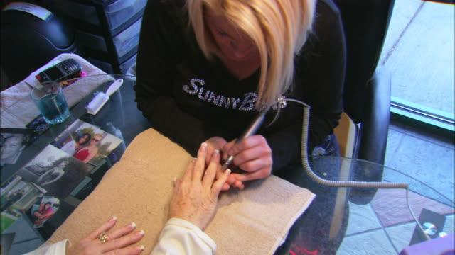 nail technician filing long fingernails of client