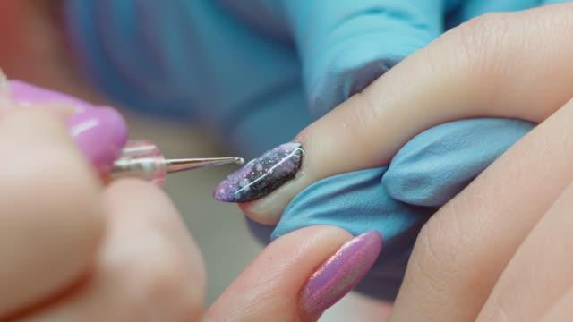 Nail technician painting client's fingernails