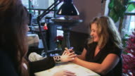 nail technician with young woman client, both sitting and dressed in black